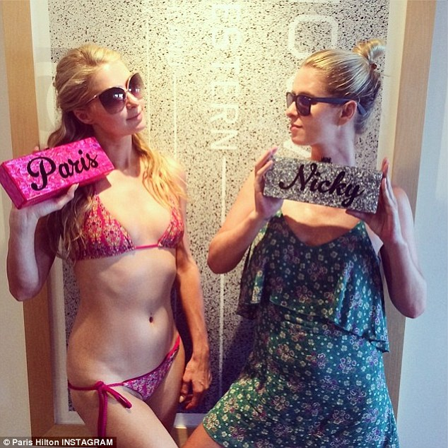 All custom everything: Paris and sister Nicky, 30, posing with customized glittering nameplates
