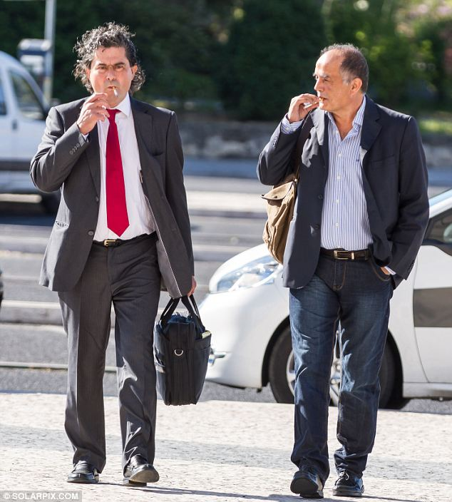 Goncarlo Amaral, right, and his lawyer smoke cigarettes before appearing in court in Lisbon today