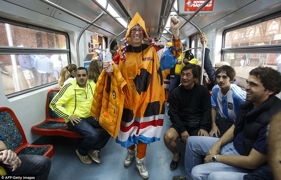Patriotic: A Netherlands fan, dressed in an inflatable footbal,l rides the express train in Sao Paulo towards the stadium ahead of the game