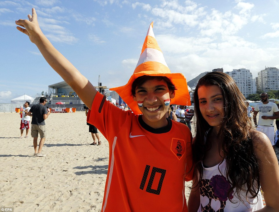 Beach: Two young Holland fans arrive on the gold sands where they watched their side take on Argentina for a place in the World Cup final