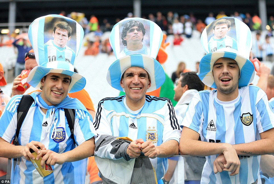 Showing their support: Three fans wear hats with photos of Lionel Messi (left and right) and Argentinian legend Maradona (centre)