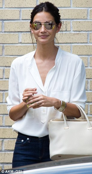 Not blending in: While she was seemingly happy to join her friends, the 28-year-old Californian stood out from the crowd in her stylish, put-together ensemble of dark skinny jeans, a white blouse and cream handbag
