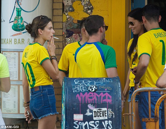 Bad habits: The women headed outside for a smoke and chatted with fellow Brazil supporters