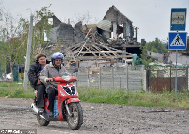 Destroyed: It comes as rebels in Donetsk have vowed to fight on against Ukranian forces who have surrounded the key eastern city. Above, a couple drive a scooter through the village of Semyonovka, near Slavyansk, today