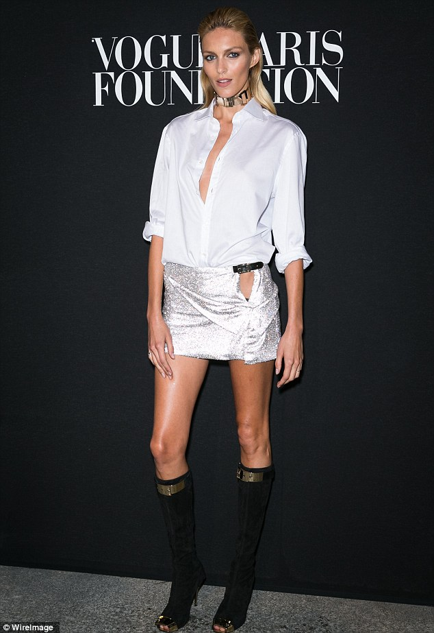 Buttoned-up: Model Anja Rubik teamed her plunging white shirt with a skimpy silver mini