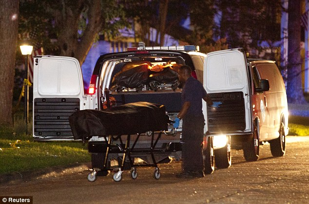 Tragedy: A Harris County Medical Examiner places one of the six bodies found in a house after several people were shot to death, into the coroner's van in the Houston suburb of Spring, in Texas early July 10, 2014