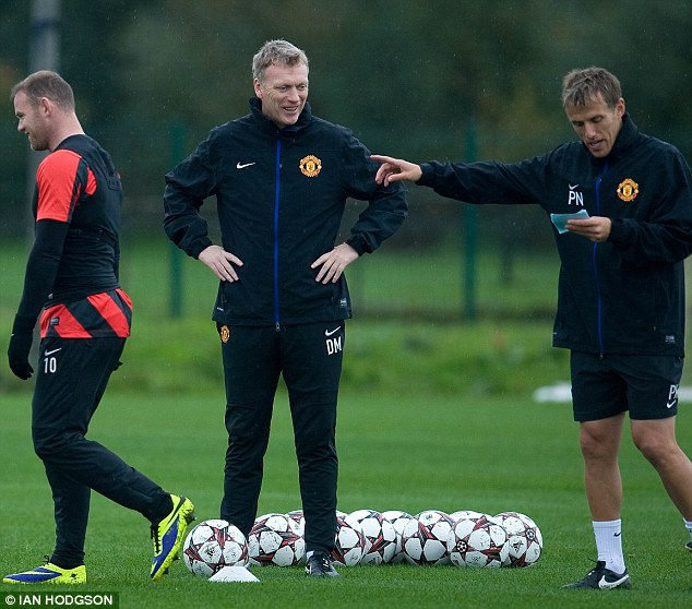 Pointing the finger: Neville in conversation with former Manchester United manager David Moyes and Wayne Rooney at a training session at Carrington last season