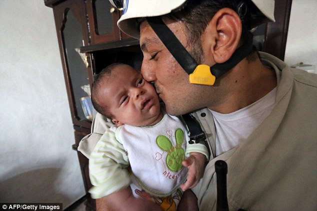 Overjoyed: Khaled, a member of Syria's Civil Defence, kisses baby Mahmud Idilbi after pulling him from rubble