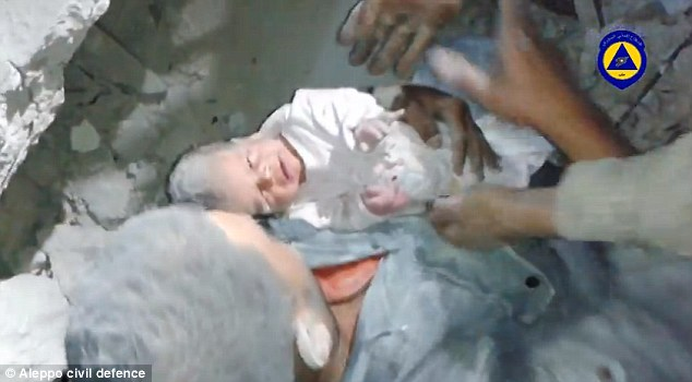 Miracle: This is the moment two-month-old Mahmud was pulled from beneath a crumbling building in Aleppo