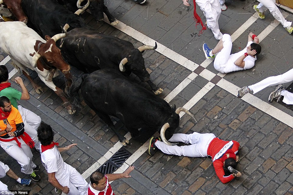 Injuries: Men fall to the pavement as they come face-to-face with fighting bulls during the San Fermin Festival