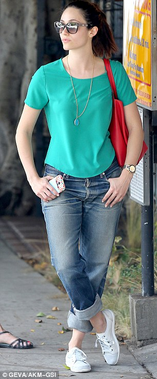 Pops of colour: The brunette beauty wore a green shirt while carrying a red handbag and blue wallet