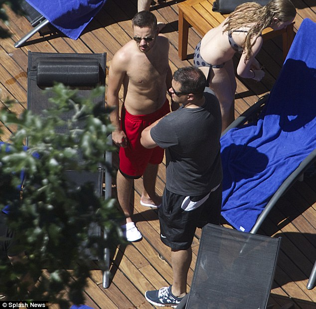 Beefing it up: Liam checks out what's going on around the pool with one of his security team nearby