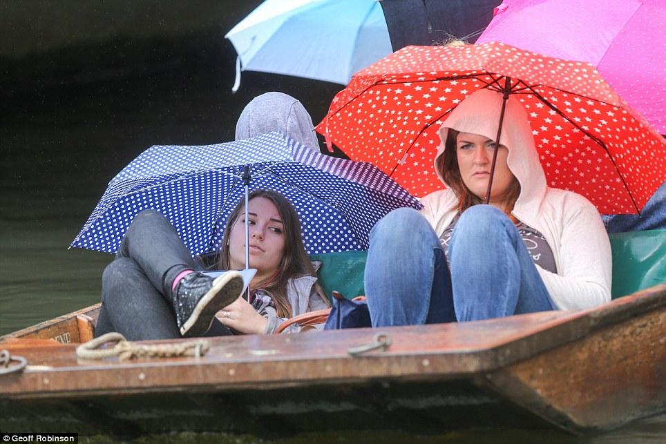 Miserable weather: Two young women hide under their umbrellas on the River Cam. A severe weather warning for rain was in place yesterday afternoon for the East