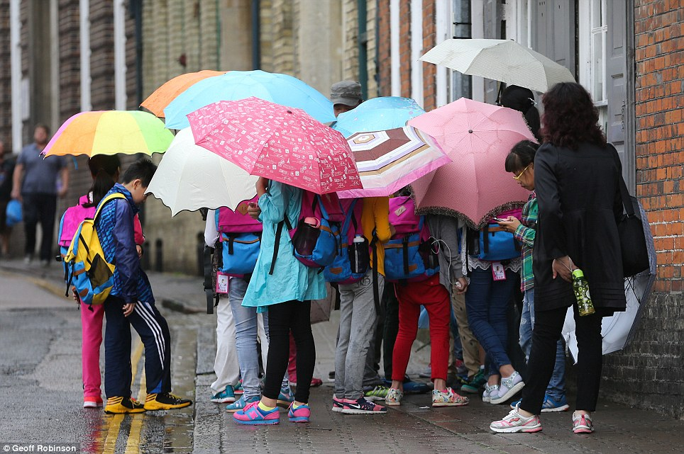 Multi-coloured umbrellas: Cambridge was one of many places in the East of England hit by rain yesterday
