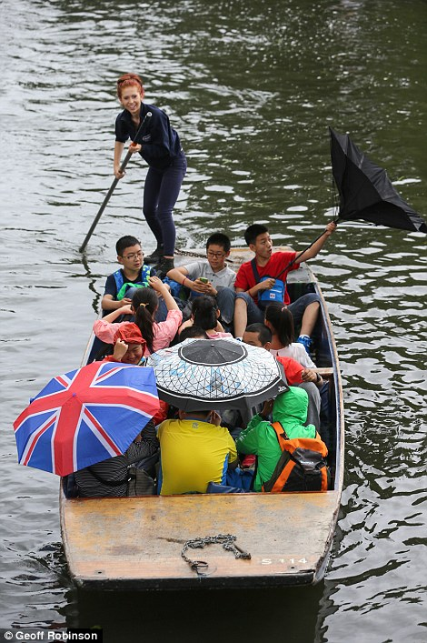 A man's umbrella blows inside out on the River Cam
