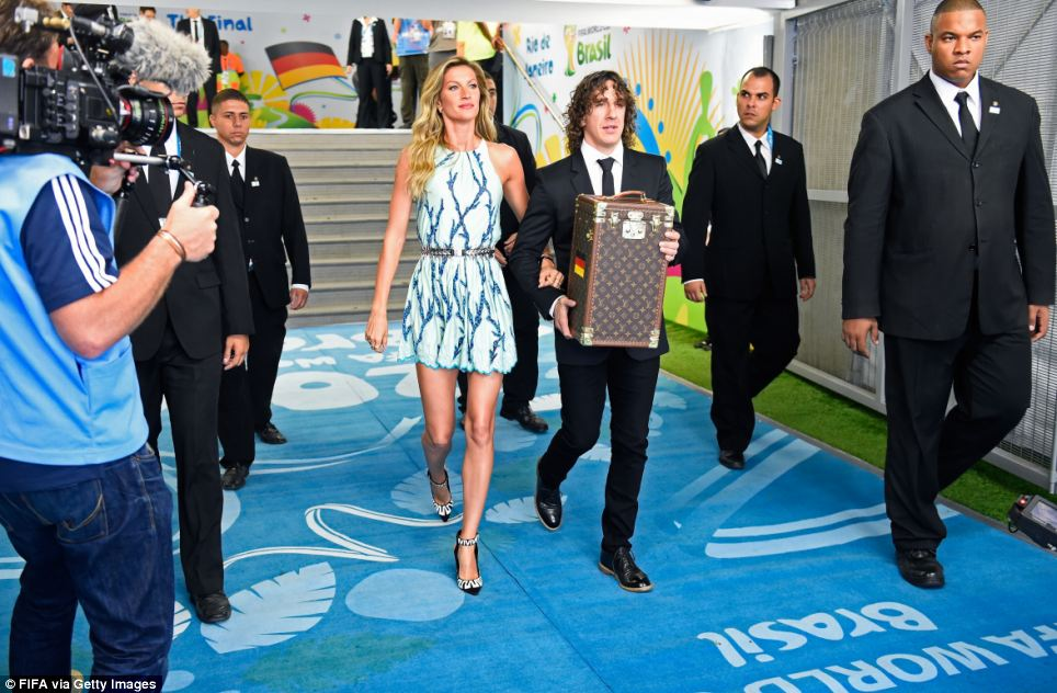 Travelling in style: Former Spanish international Carles Puyol (right) and model Gisele Bundchen (left) walk in the tunnel to present the World Cup in a special Louis Vuitton travel case