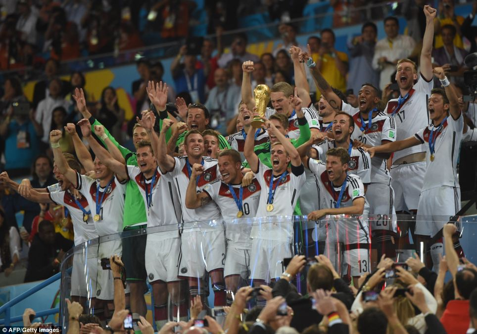 Lifting the trophy: Germany's defender and captain Philipp Lahm  holds up the World Cup trophy as he celebrates with his teammates