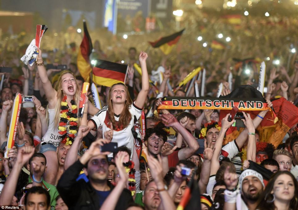 Thrilled: German fans excitedly wave their flags and scarves, cheering loudly as they mark the win at a screening in Berlin