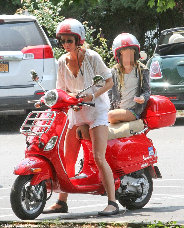 Peas in a pod: The pair donned matching red and white helmets as they zoomed around town on a bright red scooter - the 41-year-old's favoured method of transport
