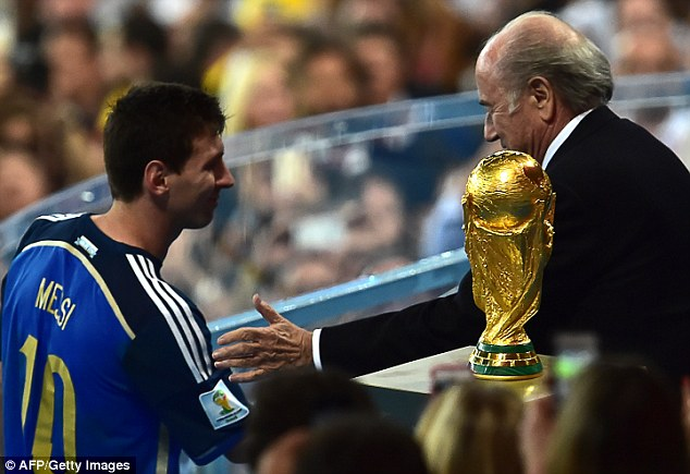 The one tat got away: Lionel Messi walks past the World Cup trophy as he shakes hands with Sepp Blatter