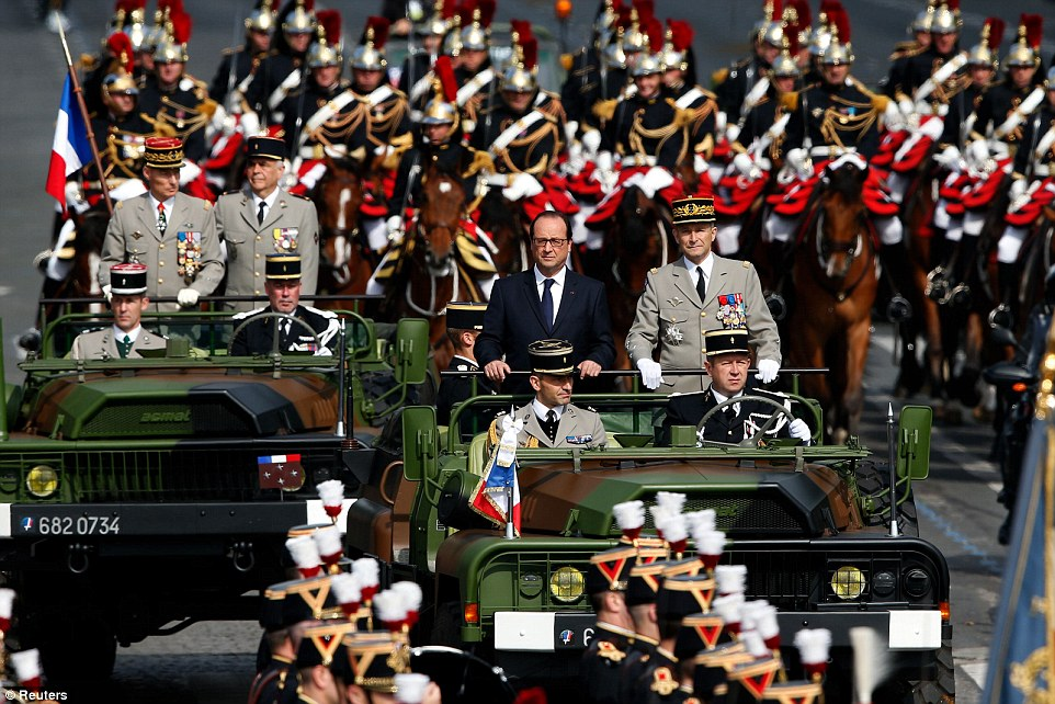 French President Francois Hollande, left, stands beside the French Army's chief of staff Pierre de Villiers, right as they review troops along the Champs Elysees