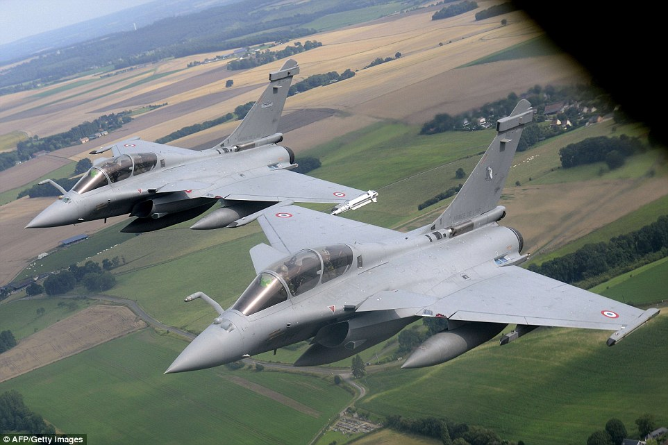 Two French Rafale fighter aircraft fly in tight formation on the wing of a Boeing C135 refueling tanker before approaching Paris for the flypast