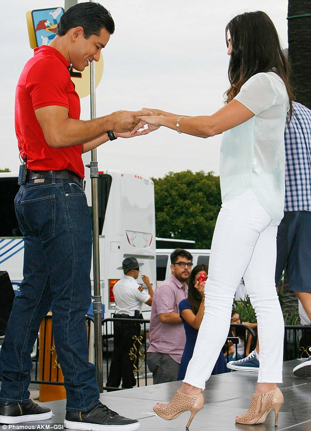 Checking her hands: Mario seemed to be looking for ring tan lines on Andi's fingers