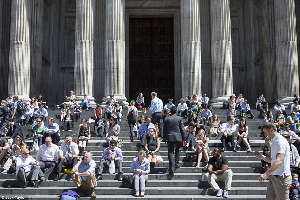 On the steps: People enjoying the good spell of weather outside St Paul's Cathedral in London today, although patches of rain in some places are expected today