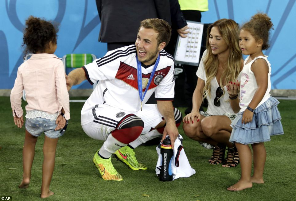 Team spirit: Götze and his girlfriend Ann-Kathrin Broemmel chat with teammate Jerome Boateng's children after their 1-0 victory over Argentina