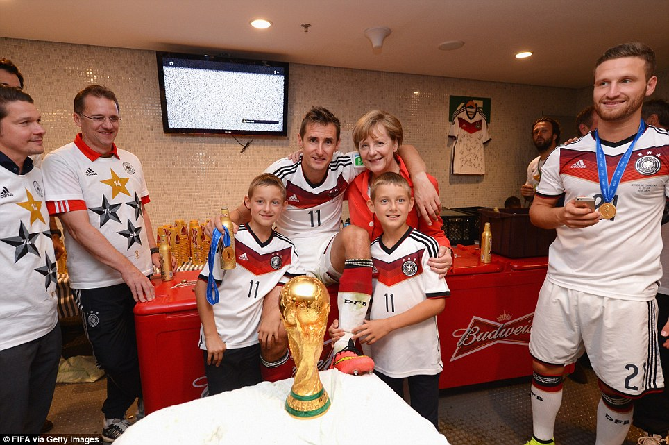 Winners: Miroslav Klose of Germany (centre) poses with Chancellor Angela Merkel and his sons Luan and Noah in the dressing room after he helped his side win the 2014 FIFA World Cup final. Klose finished the tournament as the highest scoring footballer in World Cup history