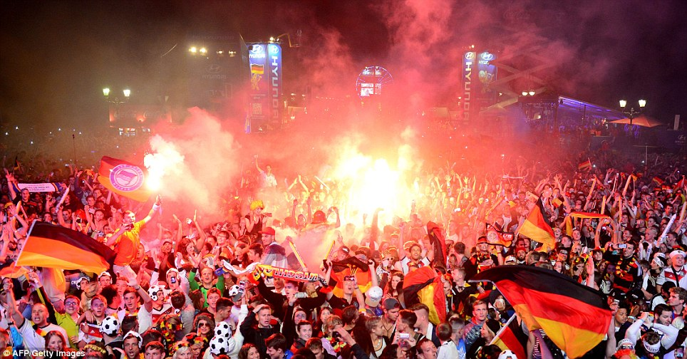 Joy: Germany fans light flares and wave flags as they celebrate their country winning the 2014 World Cup at a live outdoor screening near the Brandenburg Gate in Berlin