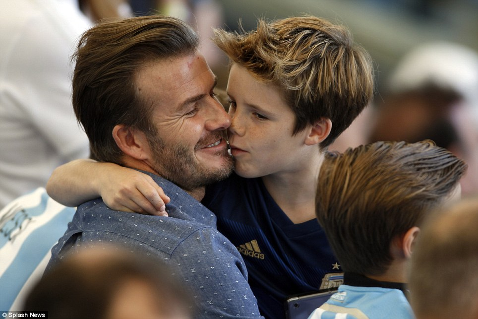 Family: David Beckham was spotted kissing his Argentina shirt wearing son Cruz as the pair watched Germany win the World Cup Final