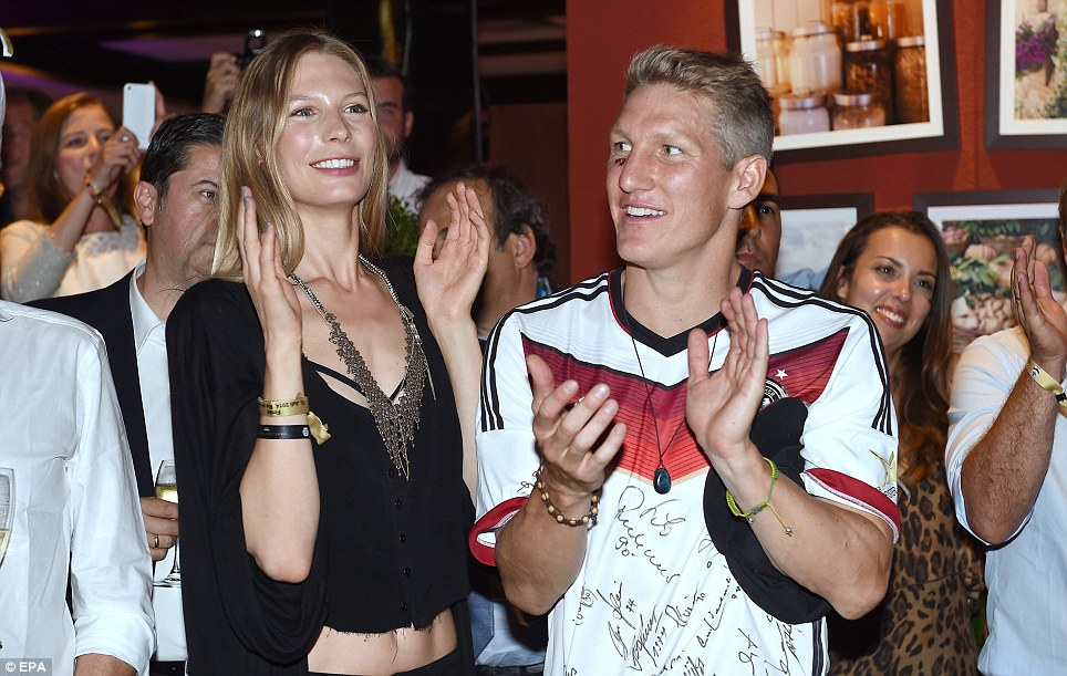 Applause all round: Bastian Schweinsteiger is pictured alongside his girlfriend Sarah Brandner during Germany's post-match party. The tireless midfielder played a key role in the game, sustaining a nasty cut below his right eye following a clash with Sergio Aguero