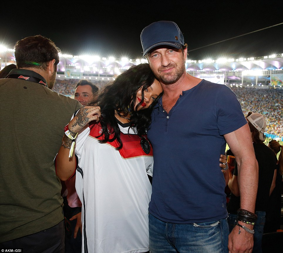 Support: Rihanna is pictured arm-in-arm with actor Gerard Butler as they watch Germany beat Argentina in the World Cup Final. Never one to shy away from controversy, Rihanna was keen to show her support for one side in particular, wearing a German national shirt for much of the match and tweeting messages about their players