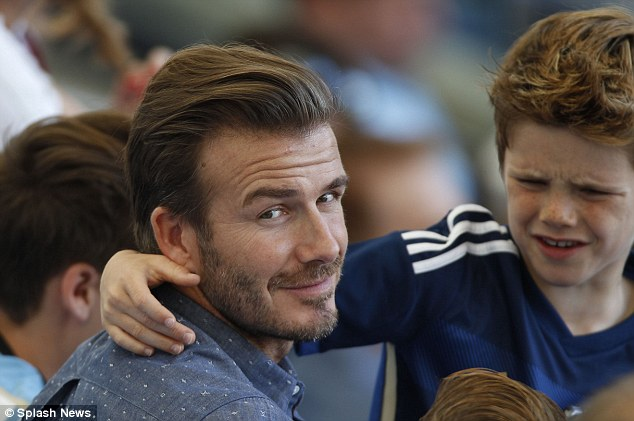 Dad duty: The former footballer prepares for a hug from youngest son Cruz