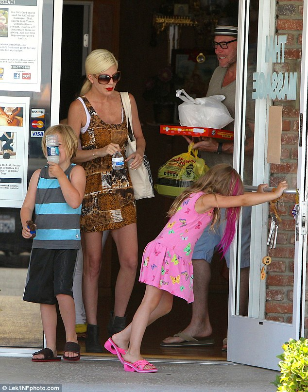 Giving daddy a hand: Little Stella held open the door for her family as Dean had his hands full