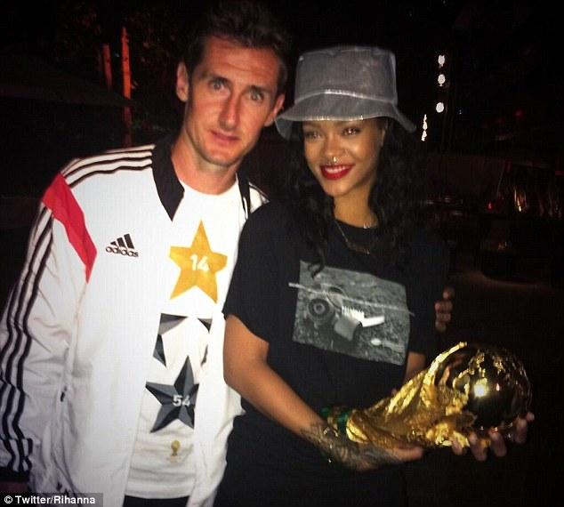 Landing the big one: Pop princess Rihanna holds the World Cup with record goalscorer Miroslav Klose