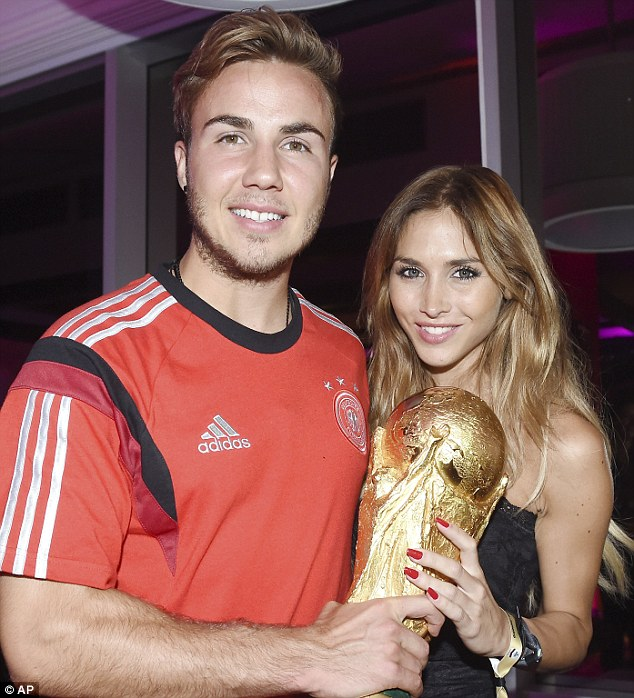 Man of the moment: Mario Gotze and his girlfriend Ann-Kathrin Broemmel celebrate with the trophy