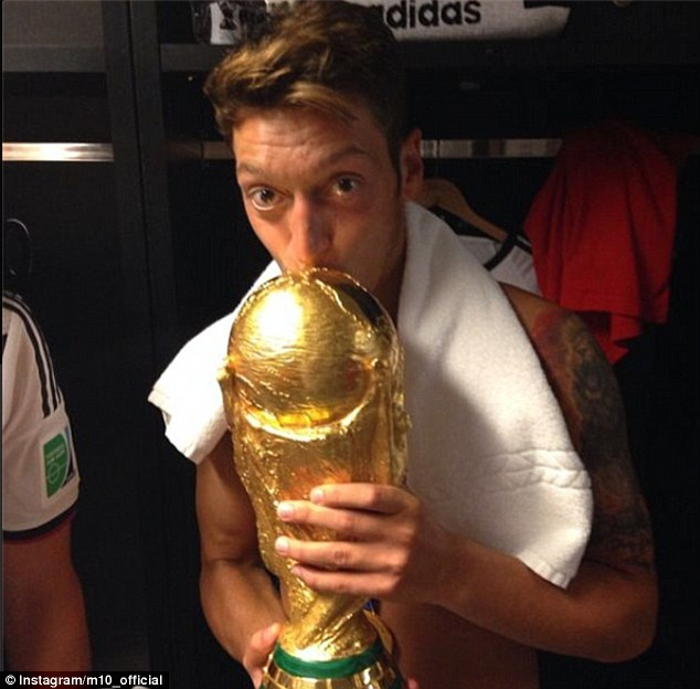 Sealed with a kiss: Mesut Ozil kisses the World Cup after the game