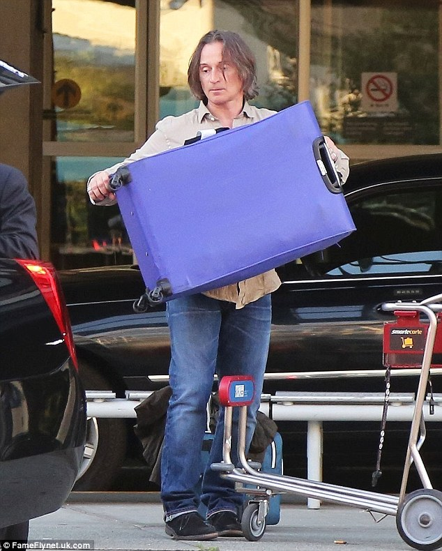 Getting a handle on it: Robert helps loads his suitcases in the car