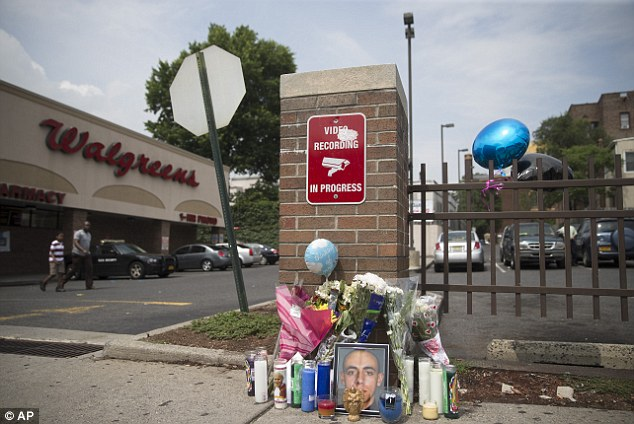 A memorial for 23-year-old Jersey City police officer Melvin Santiago stands at the Walgreens where he was fatally shot on Sunday - it is significantly smaller than that of his killer Lawrence Campbell