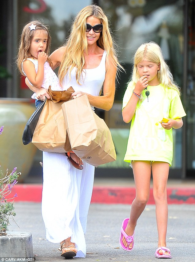 Multi-tasking mother: Denise held Eloise, her groceries and a black handbag while Lola helped out by carrying the car keys