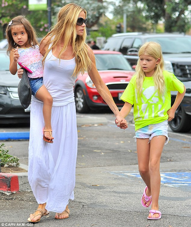 Lagging behind: Lola looked cute in a yellow tee and colourful shorts as she caught up with her mother and sister