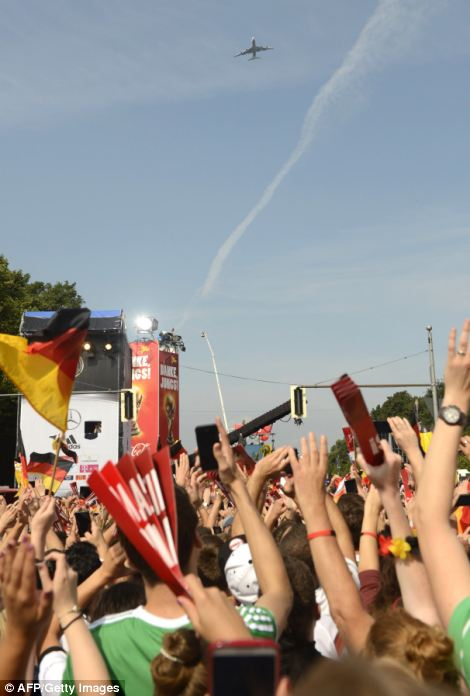 German fans cheer as the plane carrying the German national team flies over Berlin's Brandenburg Gate