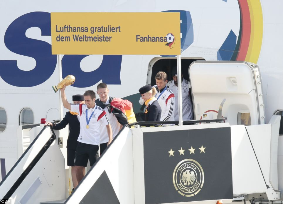 Germany's captain Philipp Lahm holds the World Cup trophy aloft as he leads teammates Sebastian Schweinsteiger, Thomas Müller and Sami Khedira, off the plane after arriving at Tegel Airport in Berlin