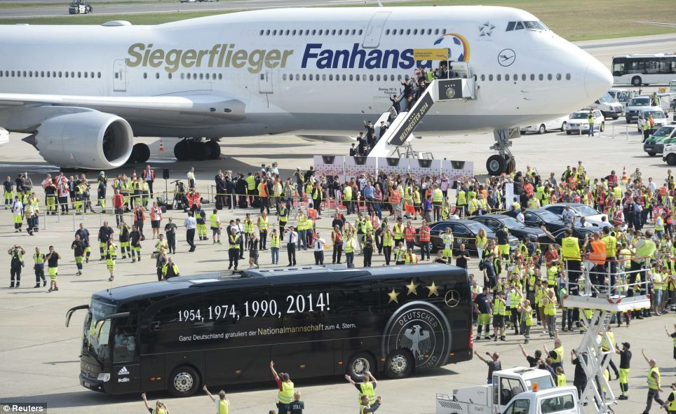 Airport staff and fans wave at the Germany football team as they leave the airport and head towards central Berlin for the homecoming party