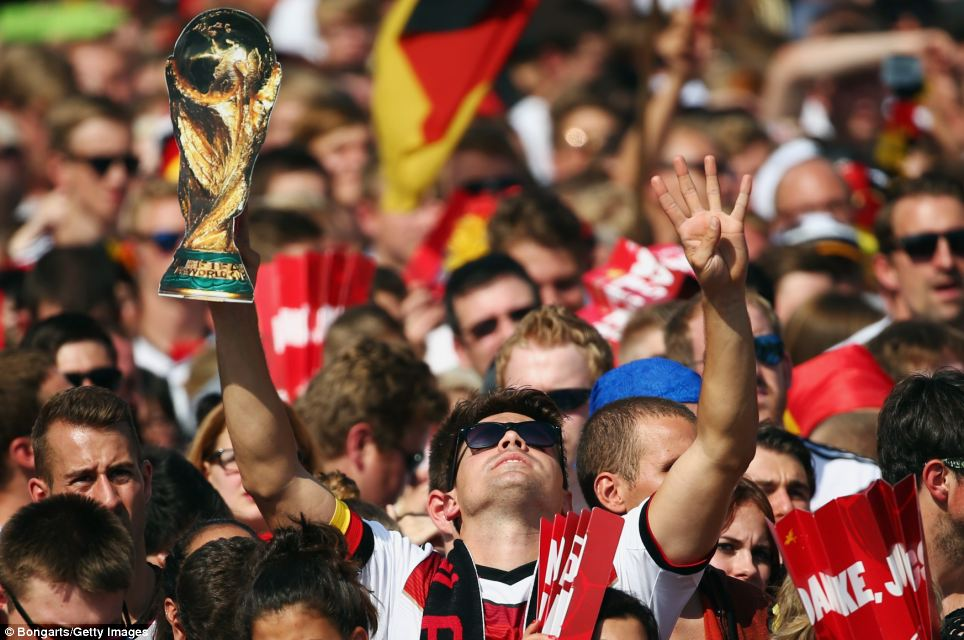 Fans enjoy the atmosphere as they wait for the players during the Germany team victory ceremony in Berlin
