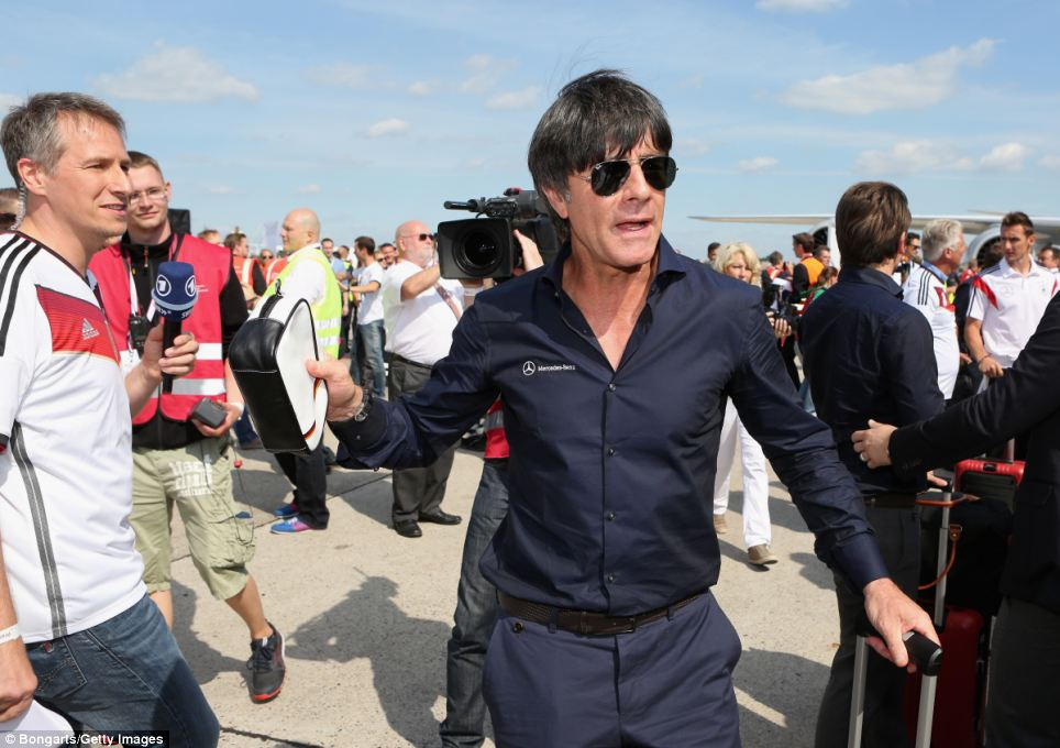 Manager Joachim Löw makes his way from the plane at Berlin Tegel Airport as the German national team return after winning the 2014 World Cup
