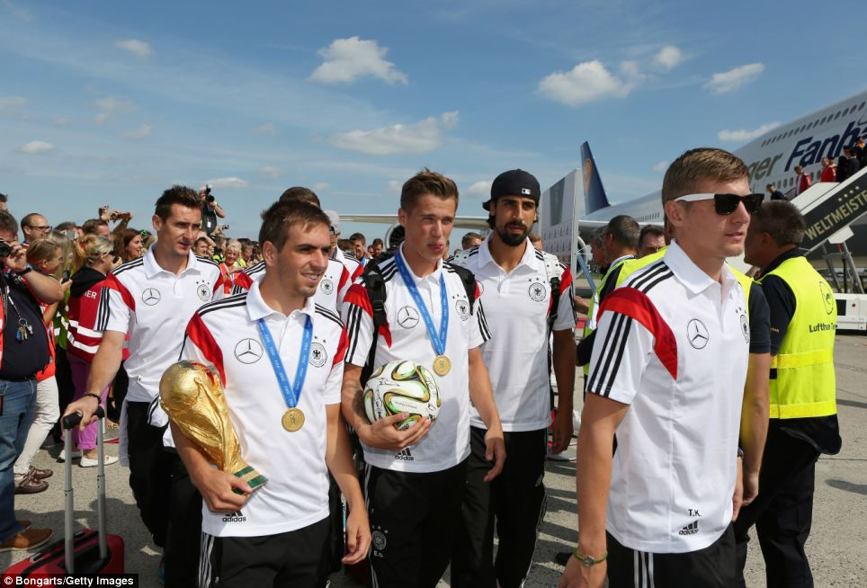 Miroslav Klose, Philipp Lahm, Lars Bender, Sami Khedira and Toni Kroos make their way from the plane with the World Cup trophy after landing at Berlin Tegel Airport