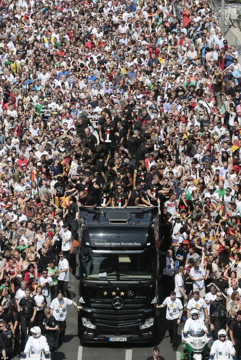 Thousands of Germany fans line the streets as the national football team makes its way through the crowds to Berlin's landmark Brandenburg Gate in an open top truck to celebrate winning the World Cup